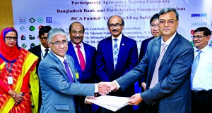 Ahmed Kamal Khan Chowdhury, Managing Director of Prime Bank Ltd (PBL) and Swapan Kumar Roy, General Manager, SME and Special Program Department of Bangladesh Bank (BB) exchange documents after signed participatory agreement of JICA sponsored Urban Building Safety Project with BB in the city on Tuesday. Fazle Kabir, Governor, SK Sur Chowdhury, Deputy Governor of BB and Takatoshi Nishikata, JICA Chief Representative to Bangladesh were present among others.