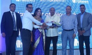 SAK Ekramuzzaman, Managing Director of Rakeen Development Company (BD) Limited, handing over a symbolic key to a flat owner of Bijoy Rakeen City in Mirpur at a ceremony on Sunday. Lt. Col (Retd.) AKM Zahurul Islam, Company Chief Operating Officer and other senior officials of the company were also present.