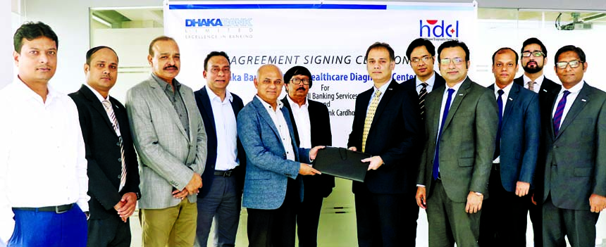 H. M Mostafizur Rahaman, SVP & Head of Cards of Dhaka Bank Limited and Halimuzzaman, Managing Director of Healthcare Diagnostic Center Ltd, exchanging documents after signing agreement at the premise of HDCL at Shyamoli in the city recently. Md. Shafquat Hossain, SEVP & Head of Retail Banking, Mukarram Hossain Chowdhury, EVP of RMG Division, Khondokar Mahedi Hasan, Manager of Board Bazar Branch of the bank and the HDCL's Directors Rezaul Karim and Abdul Hye, among others, were present.