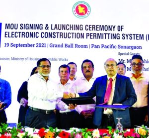 """A B M Amin Ullah Nuri, Chairman of Rajdhani Unnayan Kartripakkha (RAJUK) and Engineer Md. Sahadat Hossain Shiblu, General Secretary of IEB, exchanging document after signing a MoU on """"Electronic Construction Permitting System (ECPS)"""" on behalf of their respective organization at a city hotel on Sunday. State Minister for Housing & Public Works Sharif Ahmed M.P and Secretary of the ministry Md. Shahid Ullah Khandaker, were present."""
