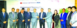 M Kamal Hossain, Managing Director of Southeast Bank Limited and Tanvir Rahman, Executive Director (Supply Chain Management) of Walton Group, exchanging an agreement signing document for online shopping of Walton products at the Bank's head office in the city recently. Top officials from both the sides were also present.