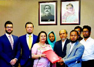 Afroza Khan, Managing Director of Moonno Fabrics Limited and Md. Robiul Islam, Senior Manager of Dhaka Stock Exchange (DSE), exchanging document after signing the re-listing agreement in the capital on Sunday to start transaction of the company's share in main market from OTC market. High officials from both the organizations were present.